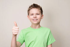 Ragazzo teenager felice con il gancio dentario smontabile che mostra pollice su più gest immagini stock