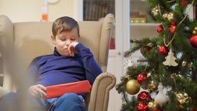 Ragazzo teenager paffuto che si siede in una sedia vicino all'albero di Natale Sta tenendo un regalo in una scatola rossa video d archivio