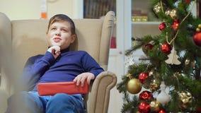 Ragazzo teenager paffuto che si siede in una sedia vicino all'albero di Natale Sta tenendo un regalo in una scatola rossa stock footage