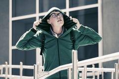 Ragazzo teenager pazzo in una maglia con cappuccio contro un edificio scolastico Fotografie Stock Libere da Diritti