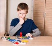 Ragazzo teenager premuroso che fa progetto elettronico della scuola nella sua stanza Immagine Stock Libera da Diritti