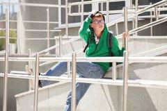 Ragazzo teenager triste in una maglia con cappuccio contro un edificio scolastico Fotografia Stock Libera da Diritti