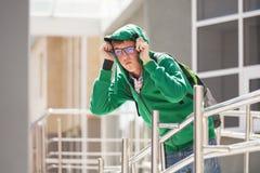 Ragazzo teenager triste in una maglia con cappuccio contro un edificio scolastico Immagine Stock Libera da Diritti