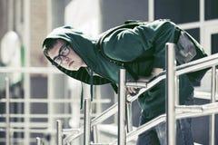 Ragazzo teenager triste in una maglia con cappuccio contro un edificio scolastico Fotografia Stock