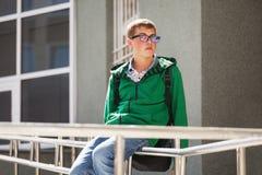 Ragazzo teenager in una maglia con cappuccio contro l'edificio scolastico Fotografie Stock Libere da Diritti