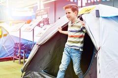 Ragazzo in tenda turistica al negozio di sport fotografie stock libere da diritti