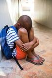 Ragazzo triste che si siede sul corridoio a scuola Fotografie Stock Libere da Diritti