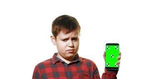 Ragazzo triste che tiene uno smartphone in sua mano con uno schermo verde video d archivio