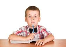 Ragazzo triste con la penna che si siede alla tavola sul taccuino isolato Fotografia Stock
