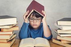 Ragazzo triste e pensieroso con i libri su una tavola Immagini Stock