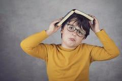 Ragazzo triste e pensieroso con un libro sulla sua testa Immagine Stock
