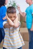 Ragazzo triste nella nuova casa mentre genitori che litigano Fotografie Stock