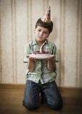 Ragazzo triste solo con la torta di compleanno sul pavimento Fotografie Stock Libere da Diritti