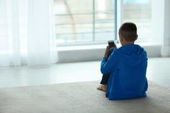 Ragazzo turbato con lo smartphone che si siede vicino alla finestra Spazio per testo immagine stock libera da diritti