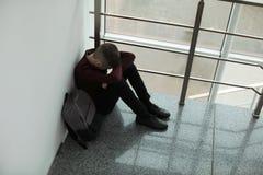 Ragazzo turbato con lo zaino che si siede vicino alla finestra all'interno fotografie stock libere da diritti