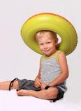 Ragazzo in un cappello da un anello di gomma Fotografia Stock