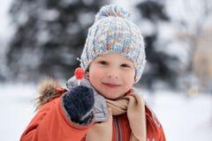 Ragazzo in un cappello tricottato di inverno con la caramella della caramella Fotografia Stock Libera da Diritti