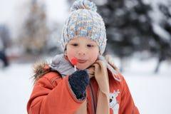 Ragazzo in un cappello tricottato di inverno con la caramella della caramella Fotografia Stock