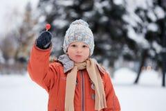 Ragazzo in un cappello tricottato di inverno con la caramella della caramella Fotografie Stock Libere da Diritti