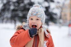 Ragazzo in un cappello tricottato di inverno con la caramella della caramella Immagine Stock