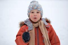 Ragazzo in un cappello tricottato di inverno con la caramella della caramella Immagini Stock