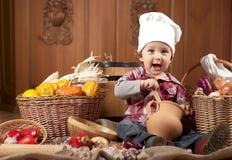 Ragazzo in un cappuccio del cuoco fra le pentole e le verdure Immagine Stock
