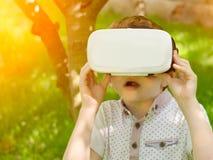 Ragazzo in un casco di realtà virtuale su un fondo di tonalità verde della foresta Fotografia Stock Libera da Diritti