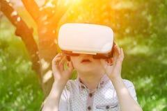 Ragazzo in un casco di realtà virtuale su un fondo di tonalità verde della foresta Immagine Stock Libera da Diritti