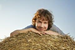 Ragazzo in un mucchio di fieno nel campo Immagine Stock