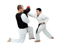 Ragazzo in una mano del colpo del battito del kimono sul simulatore nelle mani di un atleta adulto Immagini Stock