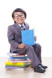 Ragazzo in vestito che legge un libro Fotografie Stock
