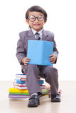 Ragazzo in vestito che legge un libro Fotografia Stock