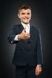 Ragazzo in vestito nero che mostra i pollici su Fotografia Stock