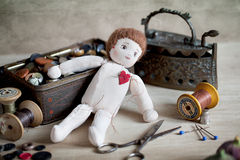 Ragdoll. Old Rag Doll on table with antique sewing utensils Royalty Free Stock Photo