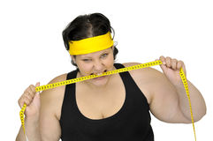 Rage. Angry large girl biting a measuring tape isolated in white Royalty Free Stock Photography
