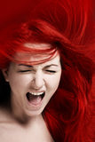 Rage. A furious young woman with her hair red like fire Stock Photography