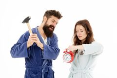Rage and hate. Early morning anxiety. Get rid of annoying alarm clock. Couple bathrobes going to destroy alarm clock and. Stay at home. Breaking rules. Man with stock photo