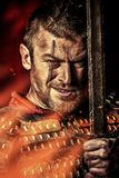 Rage man. Portrait of a courageous ancient warrior in armor with sword Stock Photo