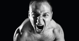 Rage scream. Strong men screaming loud over black background Royalty Free Stock Photo