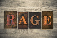 Rage Wooden Letterpress Theme. The word RAGE theme written in vintage, ink stained, wooden letterpress type on a wood grained background Stock Photos