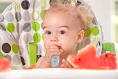 Ragged baby holding spoon itself and eating watermelon Stock Photos