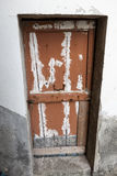 Ragged brown wooden door in a stone wall close-up of village house. Italy . Royalty Free Stock Photo