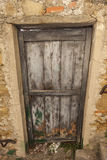 Ragged brown wooden door in a stone wall close-up of village house. Italy . Stock Photo