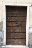 Ragged brown wooden door in a stone wall close-up of village house. Italy . Royalty Free Stock Photography