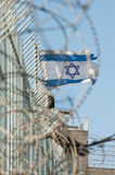 Ragged Israeli Flag. Seen through coils of razor wire, a ragged Israeli flag flies over the Jewish settlement of Beit Hoshen on the Mount of Olives in East Stock Photos
