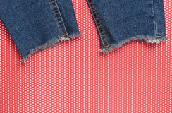 Ragged jeans on red creative backgroundin polka dot. Top view. Ragged jeans on red creative backgroundin polka dot. Top view royalty free stock image