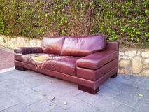 Ragged leather sofa dumped on a street. The ragged brown leather sofa dumped on a street. One large leather piece is out on the couch. It is opened yellow foam royalty free stock images