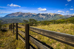 The Ragged Mountains in the fall. From Kebler Pass with a wooden split rail fence in the foreground Stock Photo