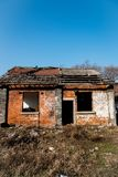 A ragged old brick house. Closeup of a ragged old brick house with blue sky stock images