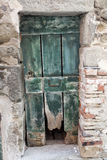 Ragged old wooden door in a stone wall. Italy Lake Garda. Entrance to an  house in the village. Stock Photos